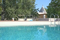 The pool with one of the trulli behind