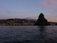 A smoking Mount Etna seen from the sea at Aci Trezza.