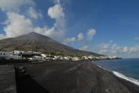 A lava sand beach under the towering peak of Stromboli.